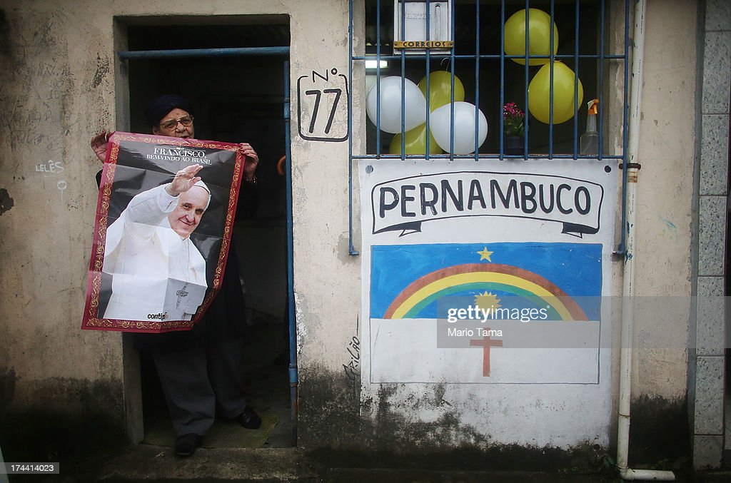 A woman displays a <a gi-track='captionPersonalityLinkClicked' href=/galleries/search?phrase=Pope+Francis&family=editorial&specificpeople=2499404 ng-click='$event.stopPropagation()'>Pope Francis</a> poster in the Varghina favela, or shantytown, before Francis arrived for a tour on July 25, 2013 in Rio de Janeiro, Brazil. More than 1.5 million pilgrims are expected to join <a gi-track='captionPersonalityLinkClicked' href=/galleries/search?phrase=Pope+Francis&family=editorial&specificpeople=2499404 ng-click='$event.stopPropagation()'>Pope Francis</a> for his visit to the Catholic Church's World Youth Day celebrations. <a gi-track='captionPersonalityLinkClicked' href=/galleries/search?phrase=Pope+Francis&family=editorial&specificpeople=2499404 ng-click='$event.stopPropagation()'>Pope Francis</a> will deliver his welcome address to the celebrations on Copacabana Beach later today as World Youth Day runs July 23-28.