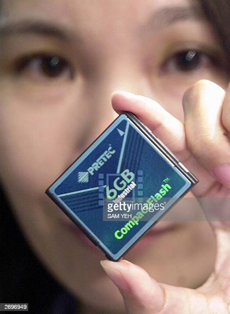 A woman displays a world latest compactflash card during Computex Online Show in Taipei 04 Novenber 2003 The card works with very low power...