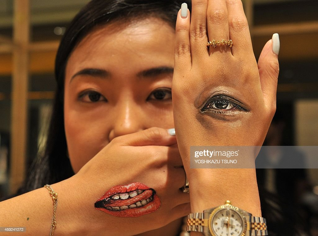 A woman displays body-paintings of her eye and her mouth on the back of her hands after Japanese body-painting artist Hikaru Cho (unseen in this picture) painted at an art event called 'Future en-nichi' in Tokyo on August 6, 2014. En-nichi is a popular Japanese summer festival and 12 contemporary artists exhibit through to August 10. AFP PHOTO / Yoshikazu TSUNO