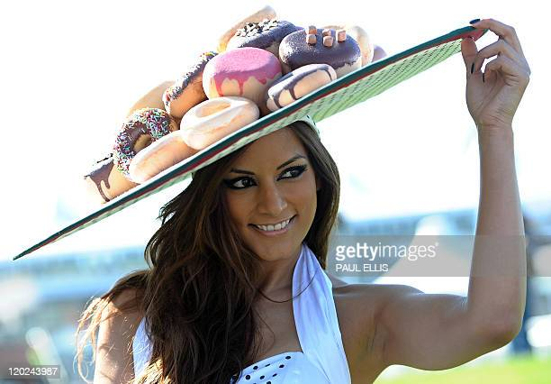 A woman displays her hat as she arrives for the second day of the Grand National meeting at Aintree Racecourse in Liverpool northwest England on...