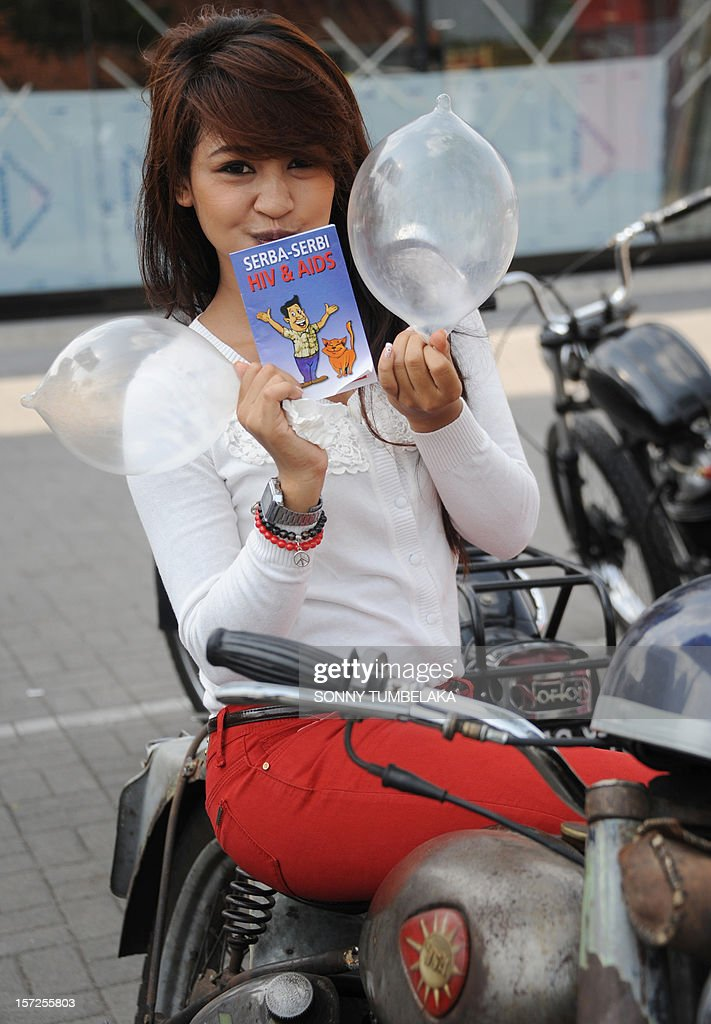 "A woman displays inflated condoms and a pamphlet during a World Aids Day campaign in Jimbaran on Bali island on December 1, 2012. The World Health Organization's (WHO) theme for World Aids Day 2012 is ""Getting to Zero: Zero new HIV infections. Zero deaths from AIDS-related illness. Zero discrimination."" AFP PHOTO / SONNY TUMBELAKA"