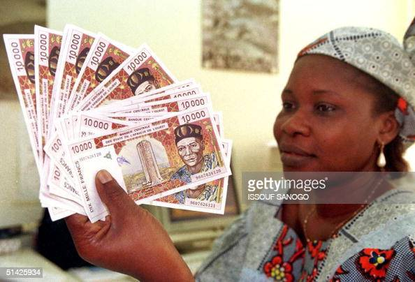 A woman displays several 10000 CFA franc about 17 US dollars bank notes 10 April in Abidjan French Finance Minister Dominique StraussKahn said today...