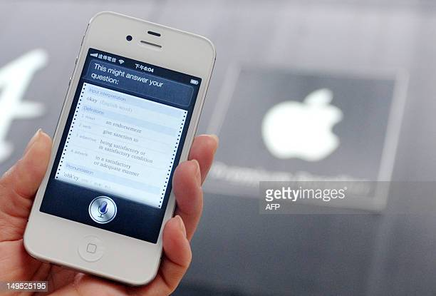A woman displays 'Siri' voiceactivated assistant technology on an Apple iPhone 4S in Taipei on July 30 2012 Taiwan's National Cheng Kung University...