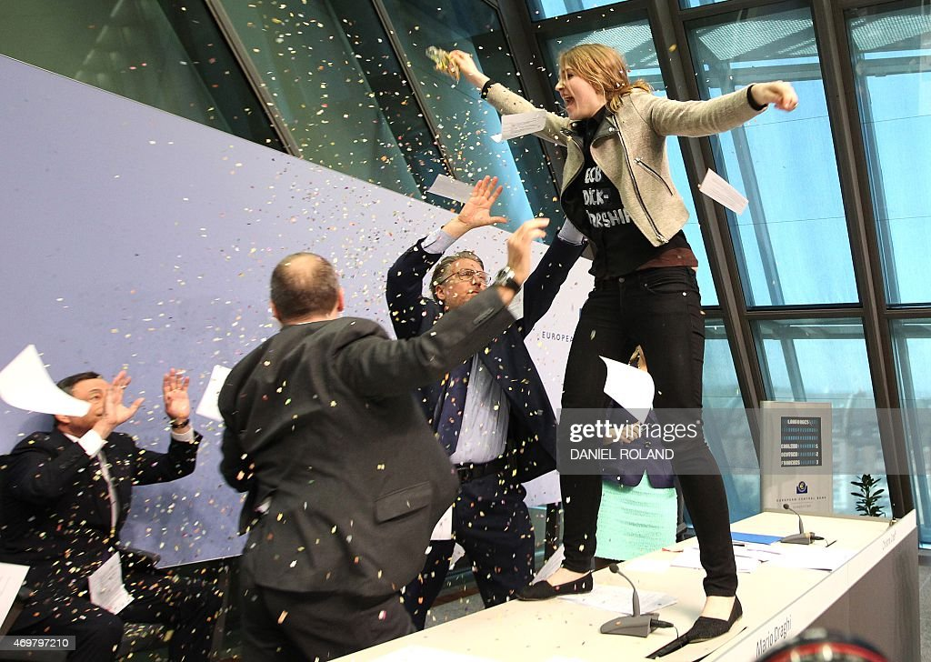 A woman disrupts a press conference by <a gi-track='captionPersonalityLinkClicked' href=/galleries/search?phrase=Mario+Draghi&family=editorial&specificpeople=571678 ng-click='$event.stopPropagation()'>Mario Draghi</a> (L), President of the European Central Bank (ECB) by throwing confettis following a meeting of the Governing Council in Frankfurt / Main, Germany, on April 15, 2015. A news conference by European Central Bank president <a gi-track='captionPersonalityLinkClicked' href=/galleries/search?phrase=Mario+Draghi&family=editorial&specificpeople=571678 ng-click='$event.stopPropagation()'>Mario Draghi</a> in the bank's headquarters was briefly interrupted Wednesday when a young woman charged at Draghi calling for an 'end to the ECB dictatorship'. AFP PHOTO / DANIEL ROLAND