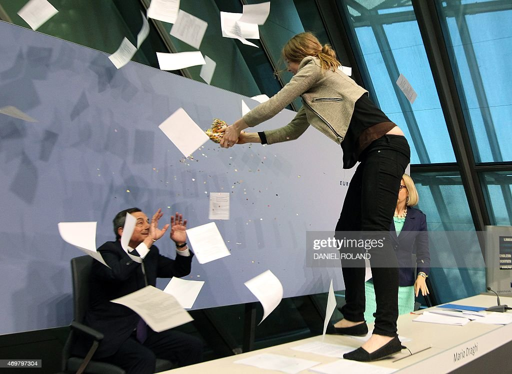 A woman disrupts a press conference by Mario Draghi (L), President of the European Central Bank (ECB) by throwing confettis following a meeting of the Governing Council in Frankfurt / Main, Germany, on April 15, 2015. A news conference by European Central Bank president Mario Draghi in the bank's headquarters was briefly interrupted Wednesday when a young woman charged at Draghi calling for an 'end to the ECB dictatorship'. AFP PHOTO / DANIEL ROLAND