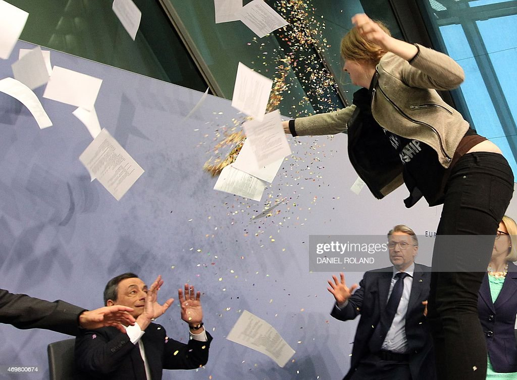 A woman disrupts a press conference by <a gi-track='captionPersonalityLinkClicked' href=/galleries/search?phrase=Mario+Draghi&family=editorial&specificpeople=571678 ng-click='$event.stopPropagation()'>Mario Draghi</a> (C), President of the European Central Bank, (ECB) following a meeting of the Governing Council ain Frankfurt / Main, Germany, on April 15, 2015. The woman who charged at Draghi calling for an 'end to the ECB dictatorship' was quickly escorted out of the premises by security officers before the news conference resumed. AFP PHOTO / DANIEL ROLAND