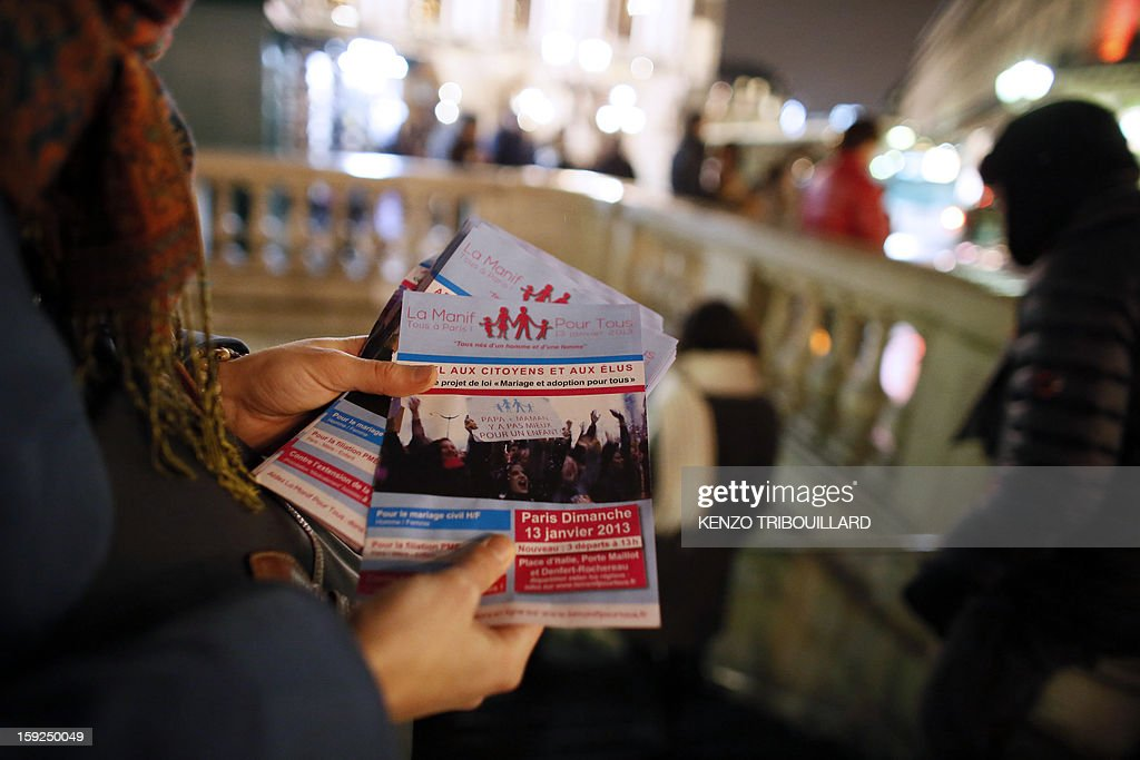 A woman distributes on January 10, 2013 in Paris flyers calling to take part in a demonstration on January 13 against gay marriage and adoption by same-sex couples. AFP PHOTO KENZO TRIBOUILLARD