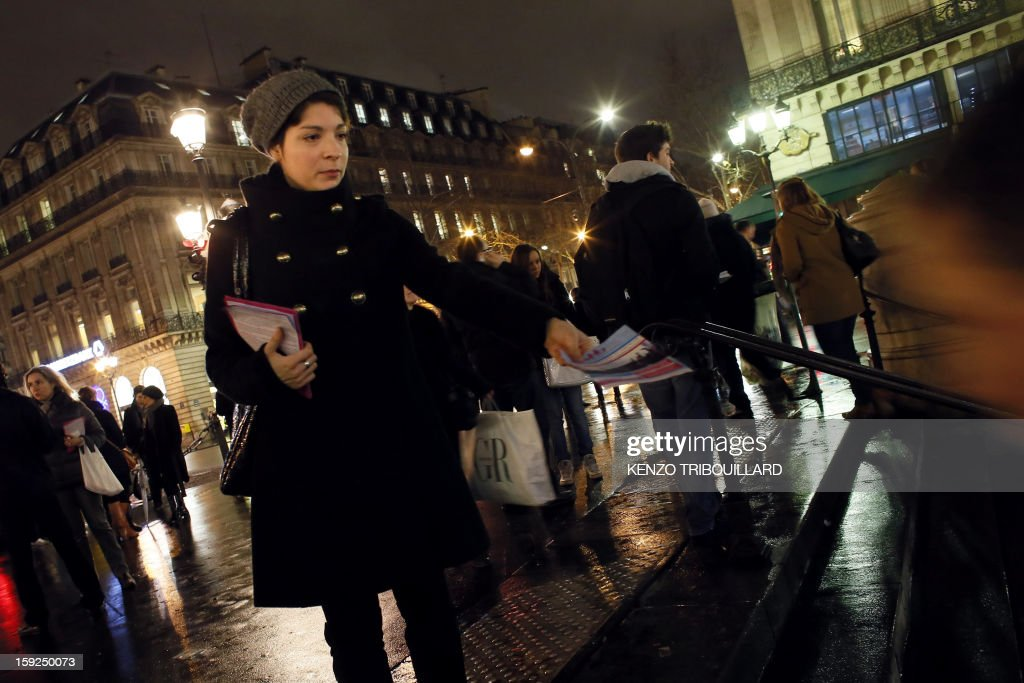 A woman distributes on January 10, 2013 in Paris flyers calling to take part in a demonstration on January 13 against gay marriage and adoption by same-sex couples.