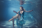 Woman in a dress dives underwater, she dances on the bottom.