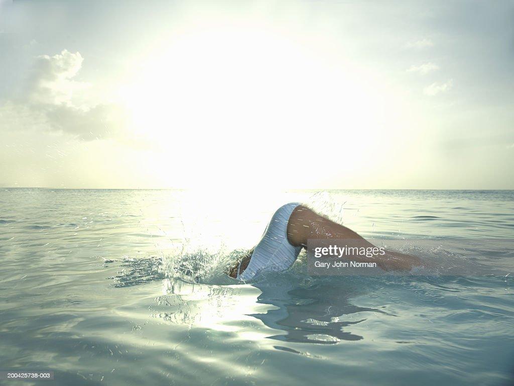 Woman diving in ocean, side view