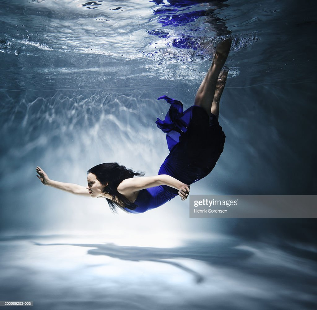 Woman diving in swimming pool, underwater, side view : Stock Photo