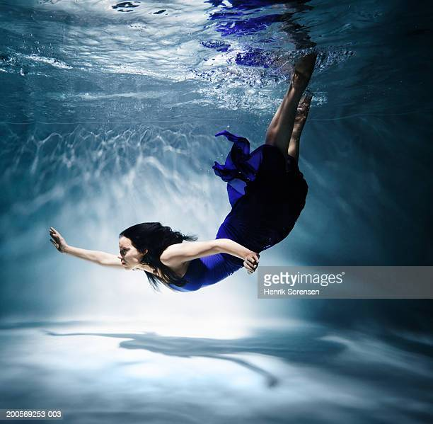 Woman diving in swimming pool, underwater, side view