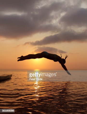 woman diving into sea at sunset : Foto de stock