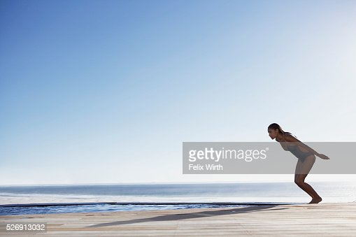 Woman diving into swimming pool : Stock Photo