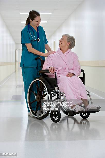 Woman Doctor Helping Woman Patient in Wheel Chair
