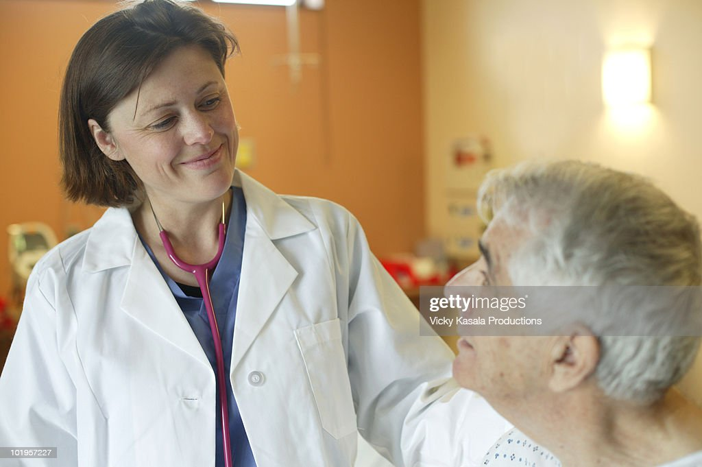 Woman doctor speaking to mature man in hospital : Stock Photo