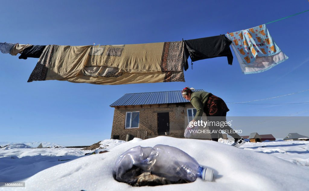 A woman does her laundry in front of her house in Ak-Ordo, a district on the outskirts of the Kyrgyzstan capital Bishkek on February 7, 2013. AFP PHOTO / VYACHESLAV OSELEDKO