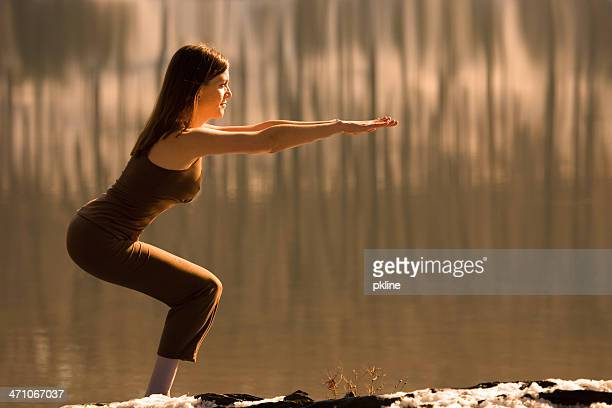 Woman does Yoga 'Chair Pose' next to a Lake