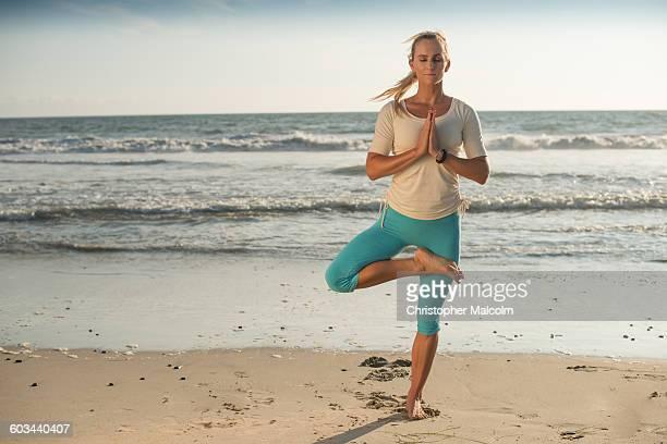 Woman does yoga on beach by ocean
