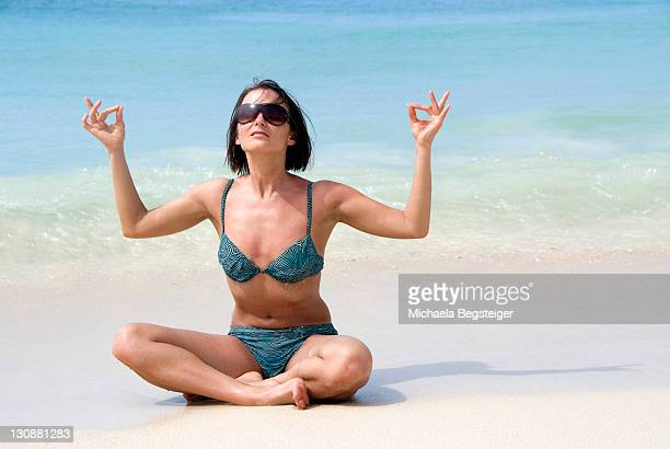 Woman does yoga on the beach