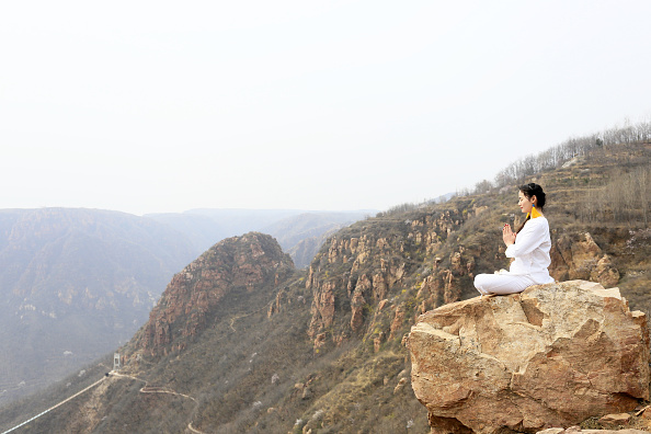 A woman does yoga on the precipice of Mount Song on March 23 2016 in Zhengzhou Henan Province of China Over 10 yoga enthusiasts practice on the...