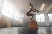 Side view image of fit young woman doing a box jump exercise. Muscular woman doing a box squat at the gym gym