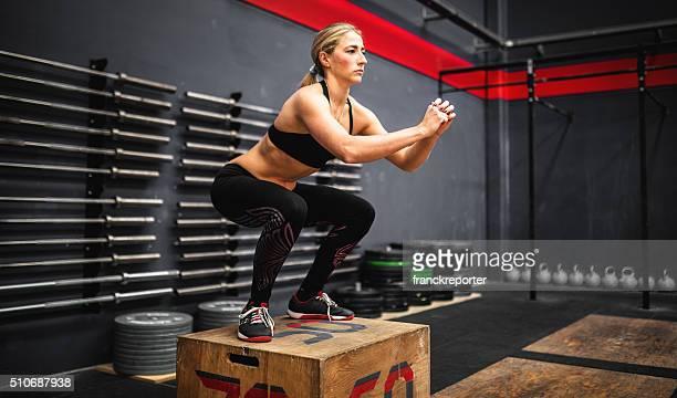 Femme faire un squat sur la boîte