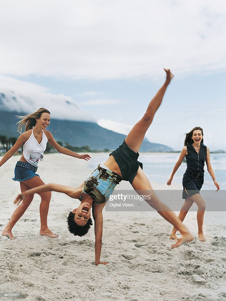 Woman Doing a Cartwheel in Front of her Two Female Friends