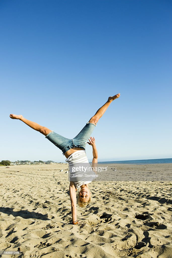 Woman doing a cartwheel in the sand. : Stock Photo