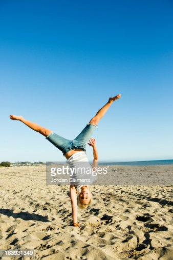 Woman doing a cartwheel in the sand.
