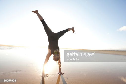 woman doing a cartwheel on the beach