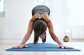 Portrait of woman practicing downward dog pose on yoga mat.  Fitness female in Adho Mukha Svanasana pose.