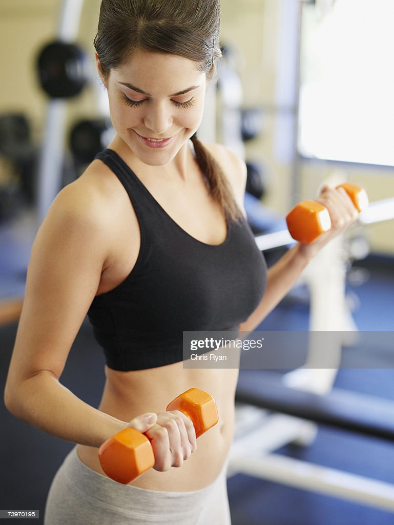 Woman doing arm curls with dumbbells : Stock Photo