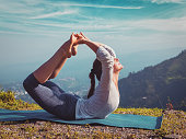 Yoga outdoors - young sporty fit woman doing Ashtanga Vinyasa Yoga asana Dhanurasana - bow pose  - in Himalayas mountains in the morning  Himachal Pradesh, India. Vintage retro effect filtered hipster