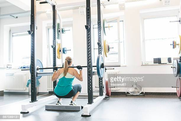 Woman doing barbell squats in a power rack