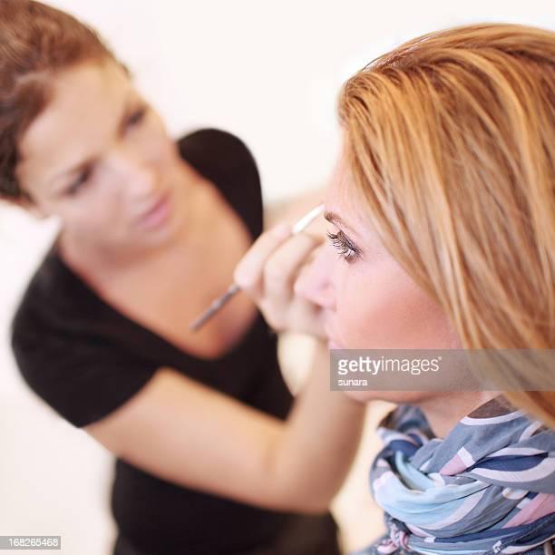 Woman doing blonde woman's makeup