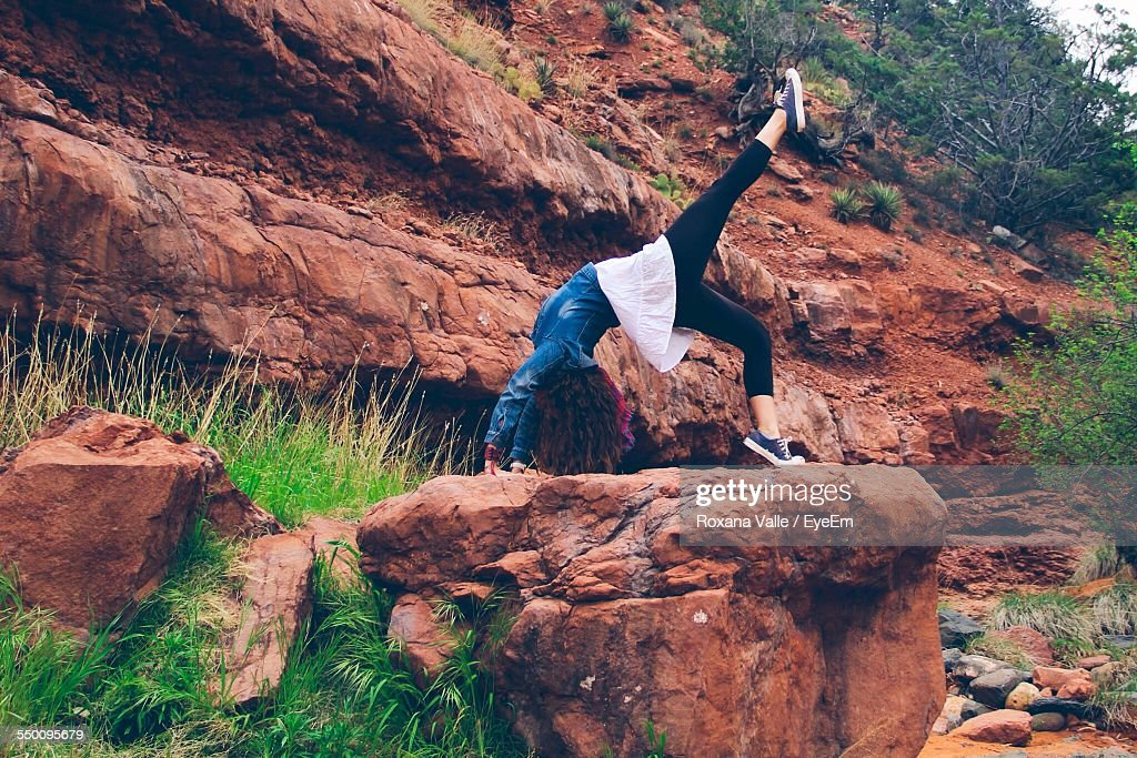 Woman Doing Bridge Position On Rocks