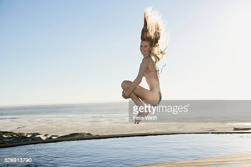 Woman doing cannonball into swimming pool : Stock Photo