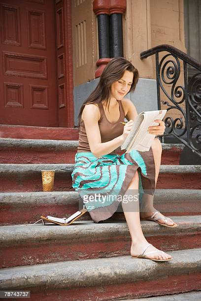 Woman Doing Crossword Puzzle on Stairs