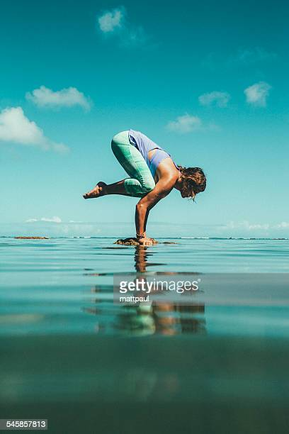 Side view of female practicing yoga on stone in water