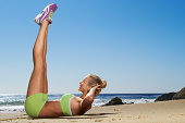 Woman doing crunch in spandex on beach