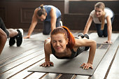 Young fit sporty woman with painful face expression doing hard difficult plank fitness exercise or push press ups feeling pain in muscles at diverse group training class in gym, endurance concept