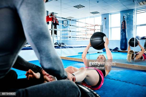 Woman doing exercise at gym with fitness trainer