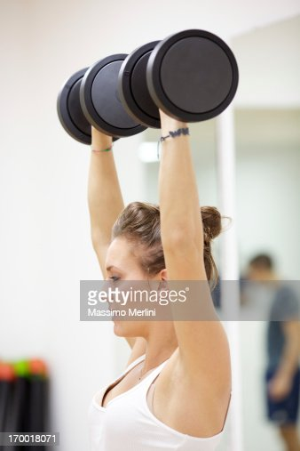 Woman doing exercise with free weights : Stock Photo