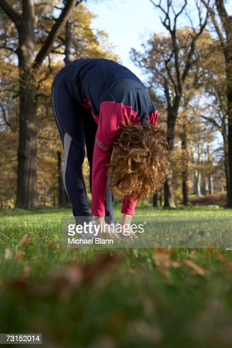Woman doing exercises outdoors, touching toes