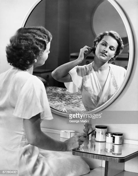 Woman doing hair in front of mirror, (B&W)