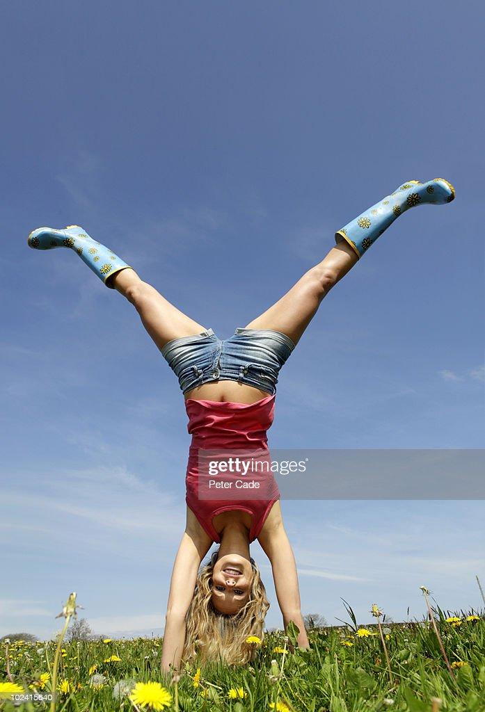 Woman doing handstand in field : Stock Photo