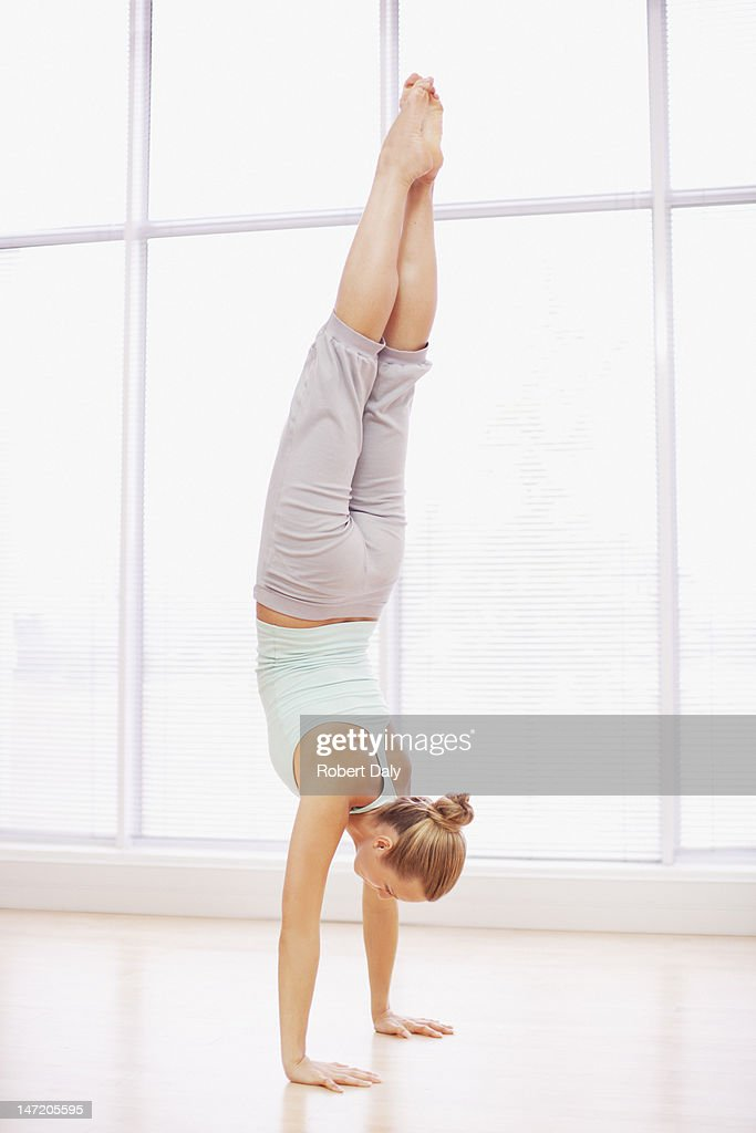 Woman doing handstand in fitness studio : Stock Photo