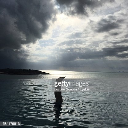 Woman Doing Handstand In Infinity Pool Against Storm Clouds