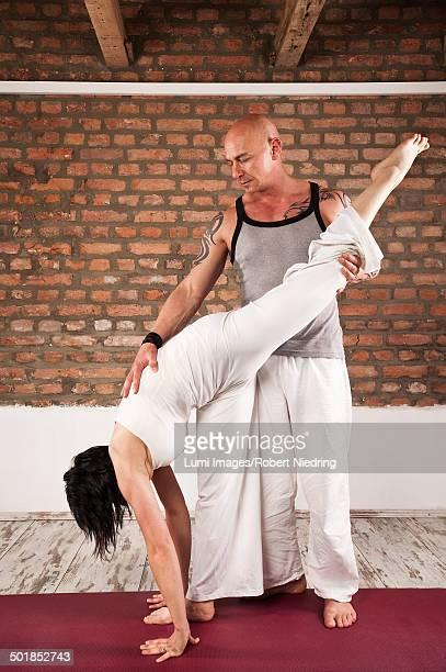 Woman Doing Handstand, Man Holding Feet